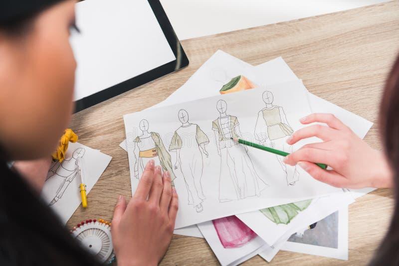 Desenhadores de moda que trabalham com os modelos dos modelos na tabela fotografia de stock
