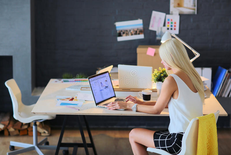 Desenhadores de moda que trabalham no estúdio que senta-se na mesa imagem de stock