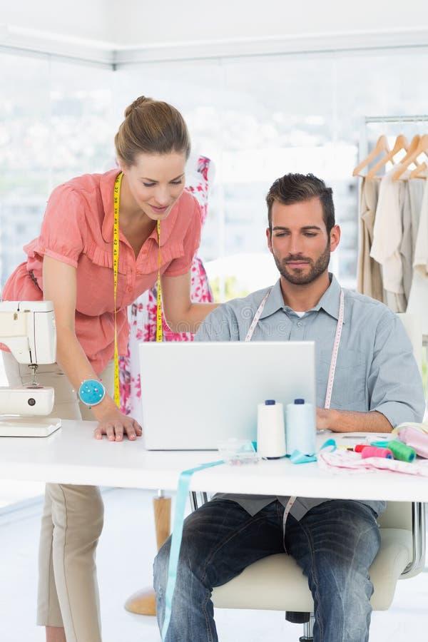 Desenhadores de moda que usam o portátil no estúdio brilhante fotos de stock royalty free