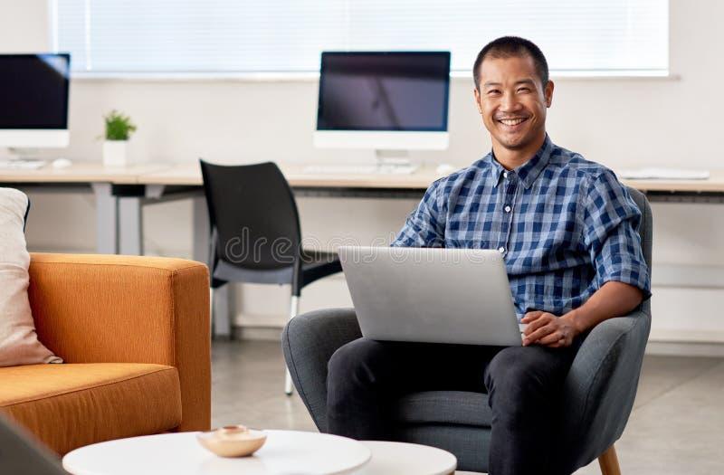 Desenhista asiático de sorriso que usa-se em um portátil no trabalho imagens de stock