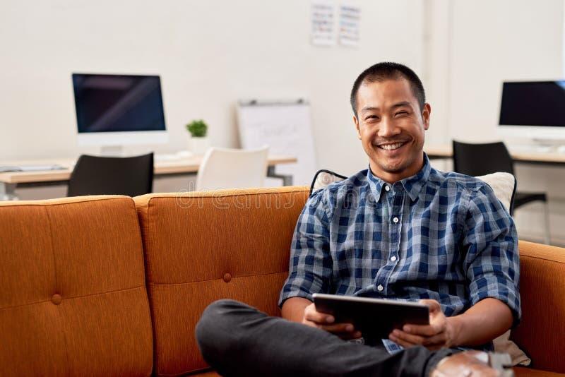 Desenhista asiático de sorriso que usa-se em uma tabuleta digital no trabalho fotografia de stock royalty free