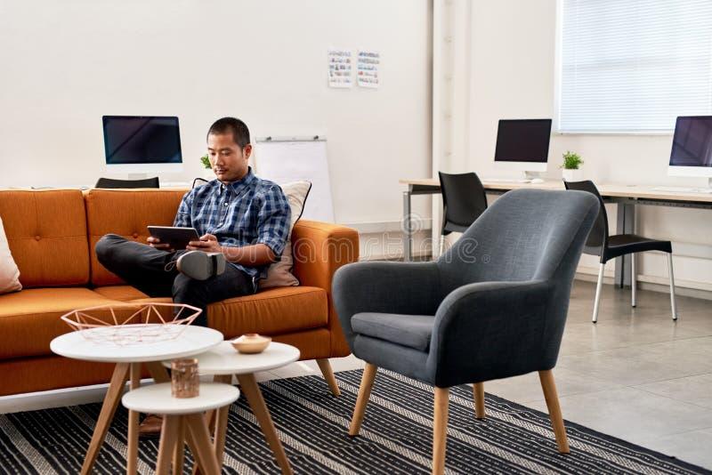 Desenhista asiático focalizado que trabalha em uma tabuleta em um escritório imagem de stock