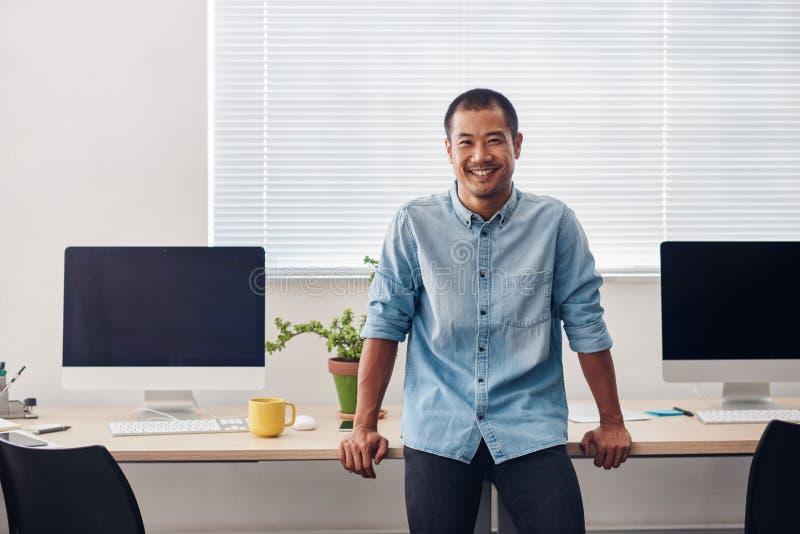 Desenhista asiático novo de sorriso que está em um escritório moderno fotografia de stock
