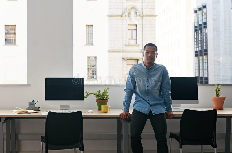 Desenhista asiático novo que está apenas em um escritório moderno fotos de stock