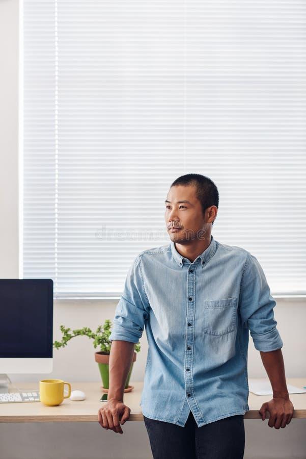 Desenhista asiático novo que está por uma mesa em um escritório fotografia de stock royalty free