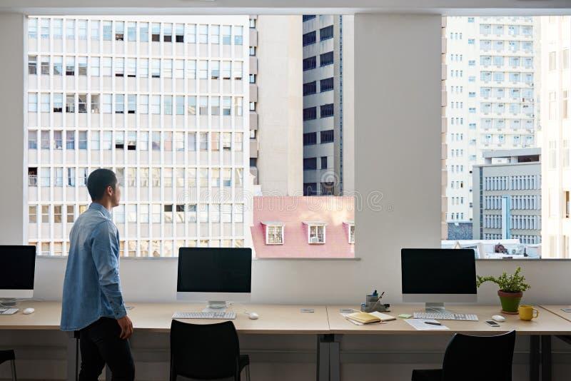 Desenhista asiático novo que olha através de uma janela na cidade imagem de stock