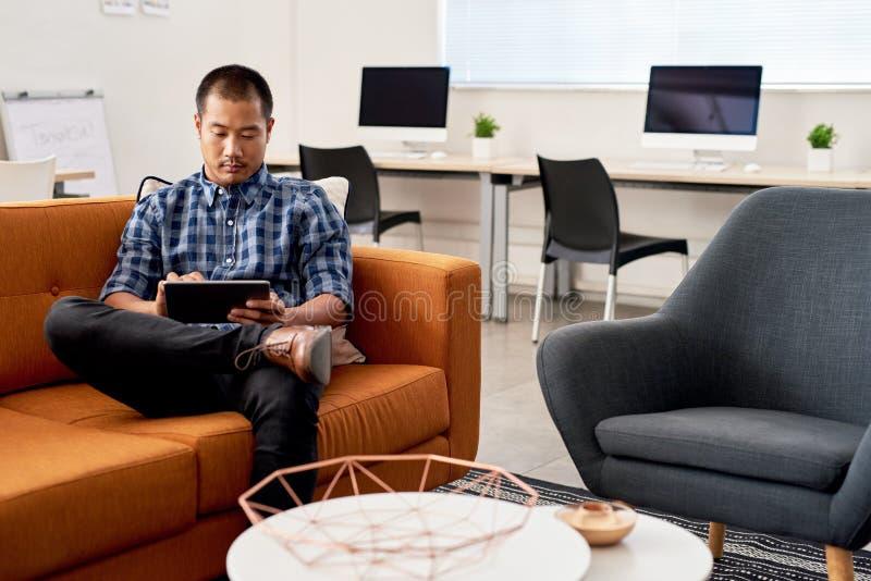Desenhista asiático novo que trabalha em uma tabuleta em um escritório imagens de stock royalty free