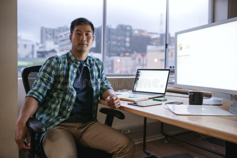 Desenhista asiático que trabalha tarde em sua mesa em um escritório imagens de stock royalty free