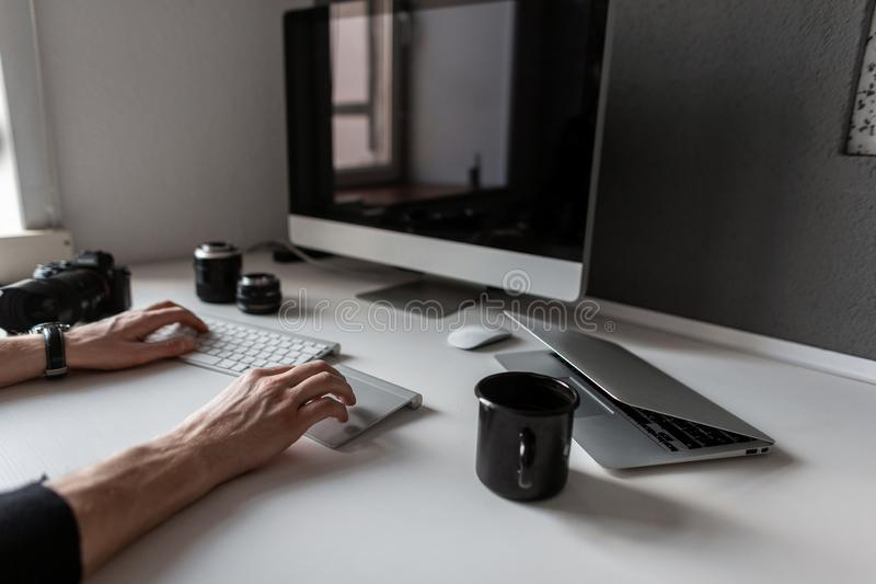 Desenhista autônomo do homem que trabalha no computador Desktop criativo com café, câmera, portátil, teclado imagem de stock royalty free