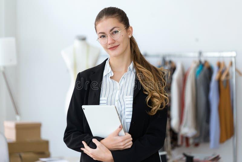Desenhista bonito da jovem mulher que olha a câmera ao guardar sua tabuleta digital em costurar a oficina foto de stock