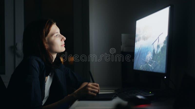 Desenhista concentrado da jovem mulher que trabalha em casa na noite usando o computador e a tabuleta de gráficos para terminar o fotografia de stock
