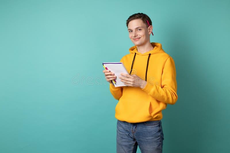 Desenhista consider?vel novo no hoodie amarelo com o caderno nas m?os e uma pena atr?s da orelha fotografia de stock royalty free