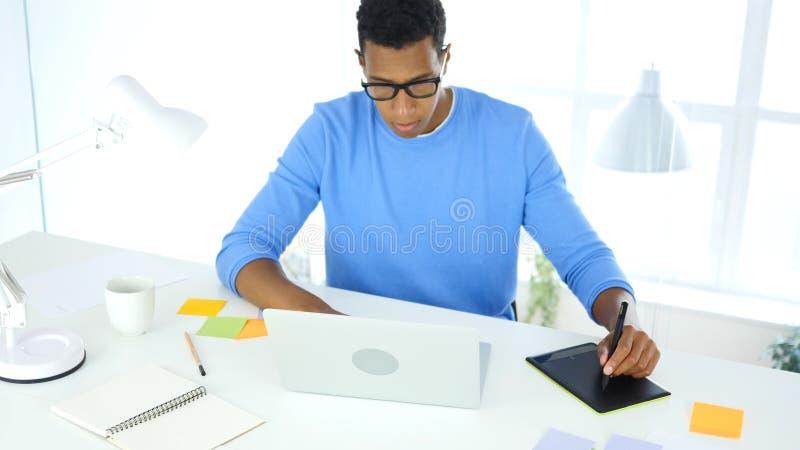 Desenhista criativo afro-americano que trabalha com a tabuleta gráfica no portátil fotos de stock