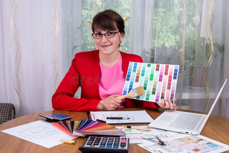 Desenhista criativo com os lápis no cabelo que mostra a paleta de cor fotografia de stock royalty free