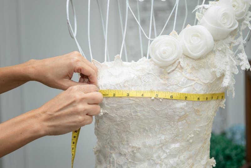 Desenhista da costureira que trabalha com o manequim no vestido de casamento imagens de stock