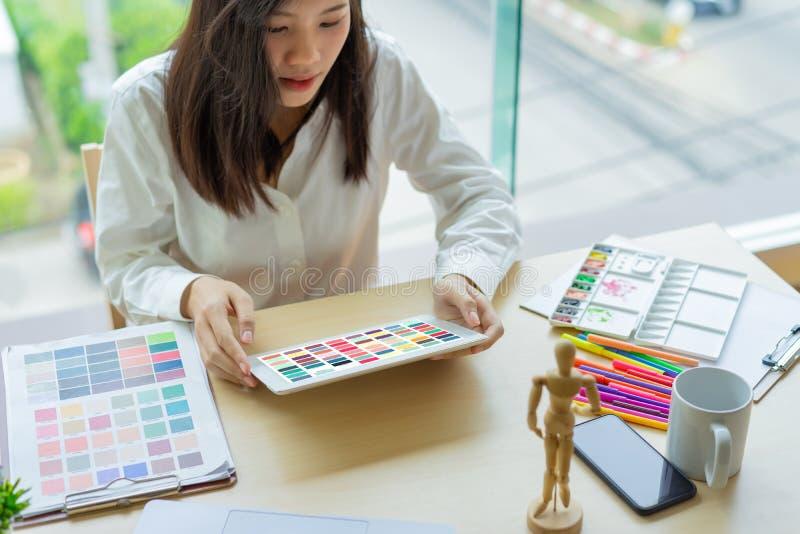 Desenhista da jovem mulher que trabalha com as amostras da cor para a seleção na mesa de escritório foto de stock