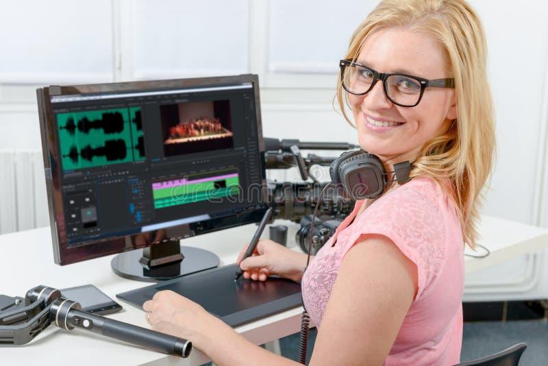Desenhista da jovem mulher que usa o computador para a edição video imagens de stock