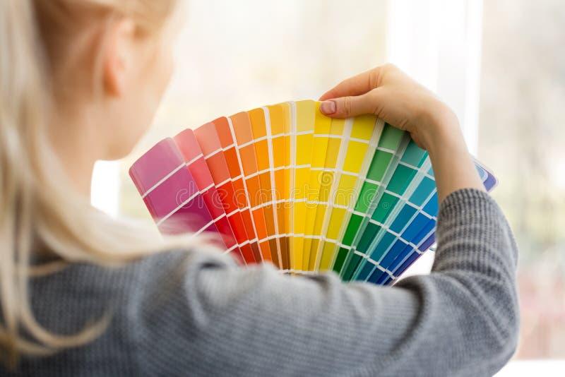 Desenhista da mulher que escolhe a cor do projeto do palett da amostra de folha imagem de stock royalty free