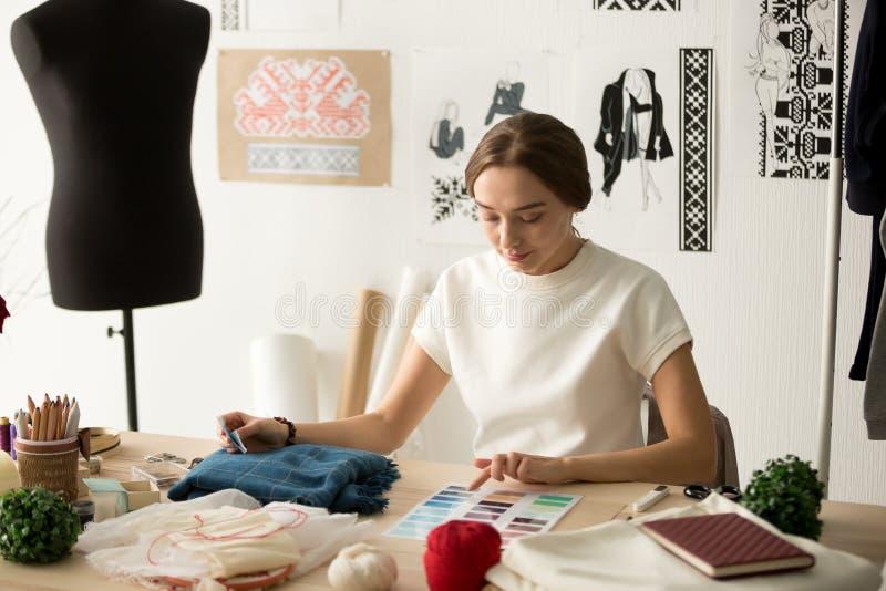 Desenhista de roupa fêmea que trabalha com as amostras na oficina imagem de stock royalty free