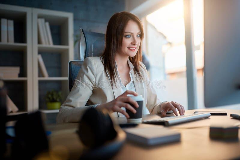 Desenhista de sorriso da mulher de negócios no trabalho que trabalha no computador para n imagens de stock royalty free