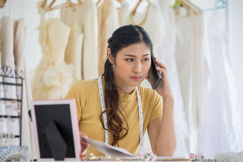 Desenhista do vestido de casamento que trabalha com o telefone esperto no salão de beleza do casamento da loja da forma foto de stock royalty free