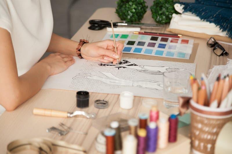 Desenhista fêmea da roupa que esboça com a escova no local de trabalho fotografia de stock royalty free