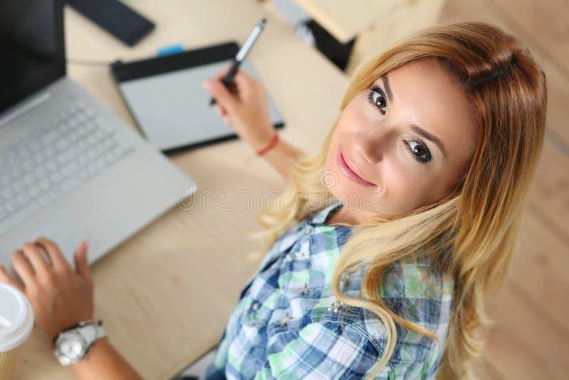Desenhista fêmea no escritório que trabalha com a tabuleta gráfica digital foto de stock royalty free
