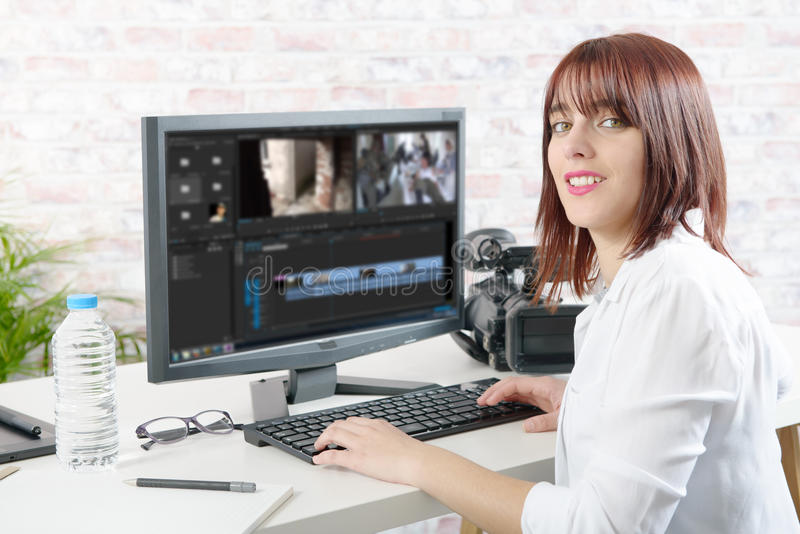 Desenhista fêmea novo que usa o computador para a edição video fotos de stock royalty free