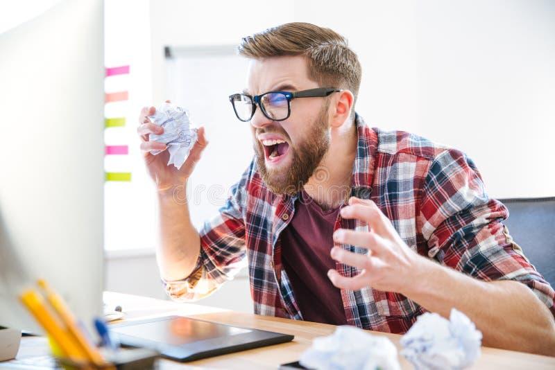 Desenhista louco irritado que grita e papel de amarrotamento em seu local de trabalho fotografia de stock