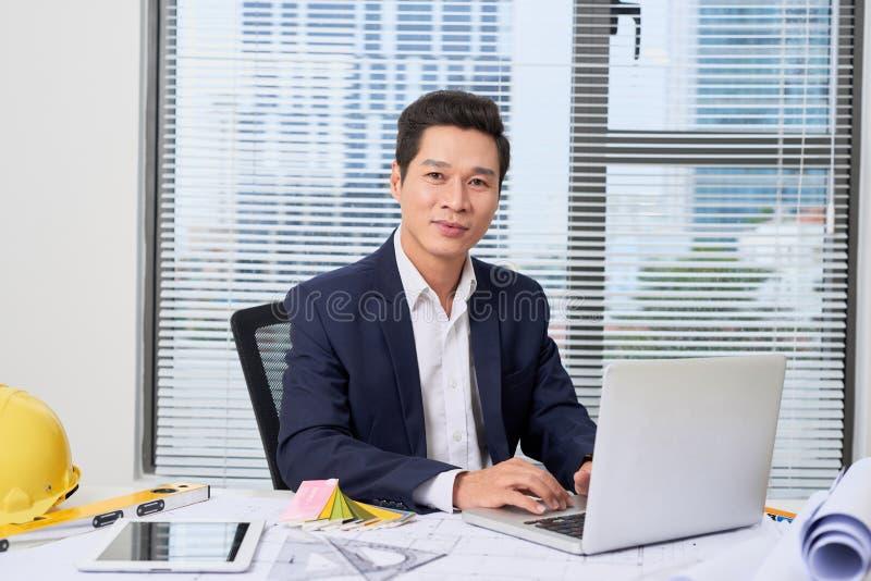 Desenhista masculino no escritório que trabalha no projeto dos arquitetos foto de stock royalty free