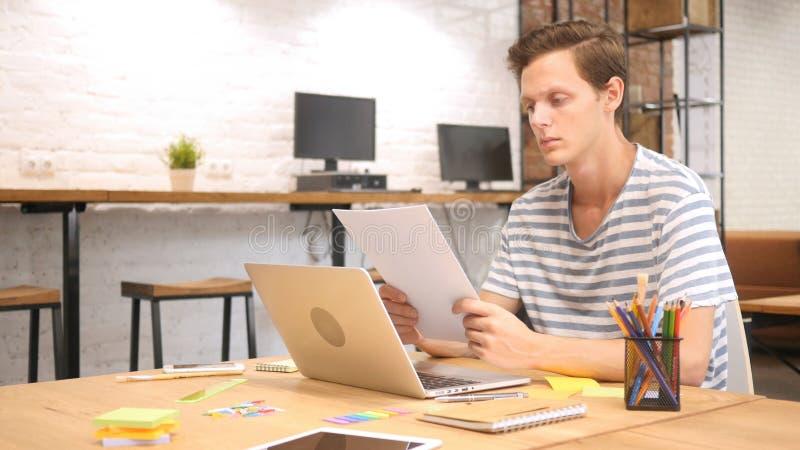 Desenhista novo Reading Paperwork na mesa no escritório do sótão imagem de stock royalty free