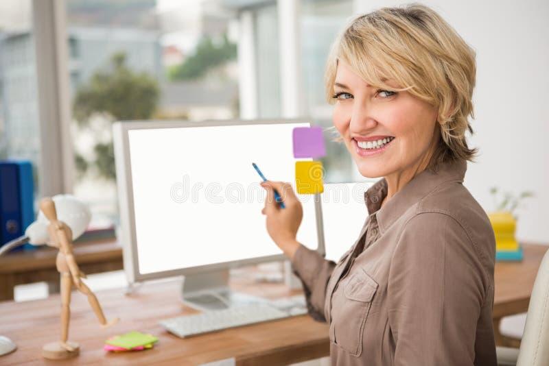 Desenhista ocasional de sorriso que aponta o tela de computador vazio foto de stock
