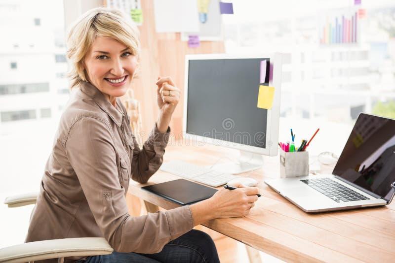 Desenhista ocasional de sorriso que senta-se na mesa imagens de stock royalty free