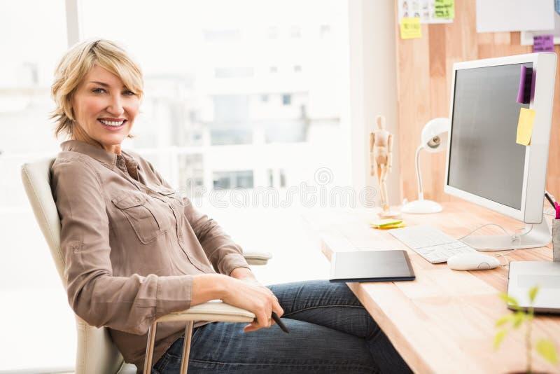 Desenhista ocasional de sorriso que senta-se na mesa fotos de stock