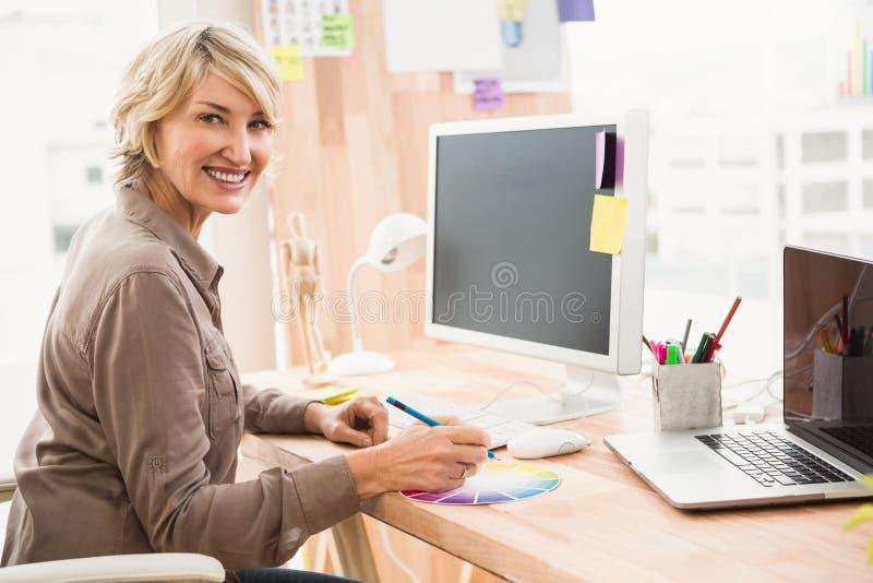 Desenhista ocasional de sorriso que trabalha com carta de cor fotografia de stock