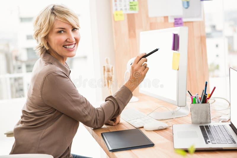Desenhista ocasional de sorriso que trabalha em sua mesa fotografia de stock