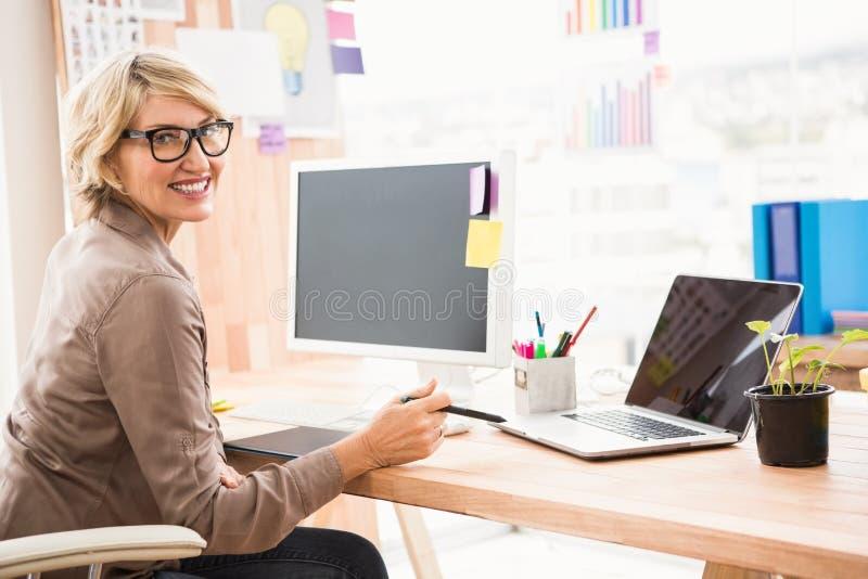 Desenhista ocasional de sorriso que trabalha em sua mesa imagem de stock royalty free