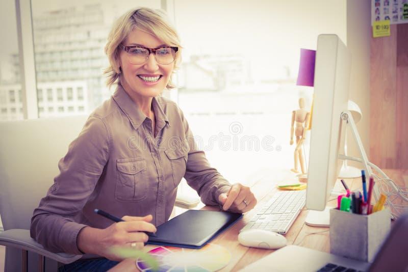 Desenhista ocasional de sorriso que trabalha em sua mesa imagem de stock
