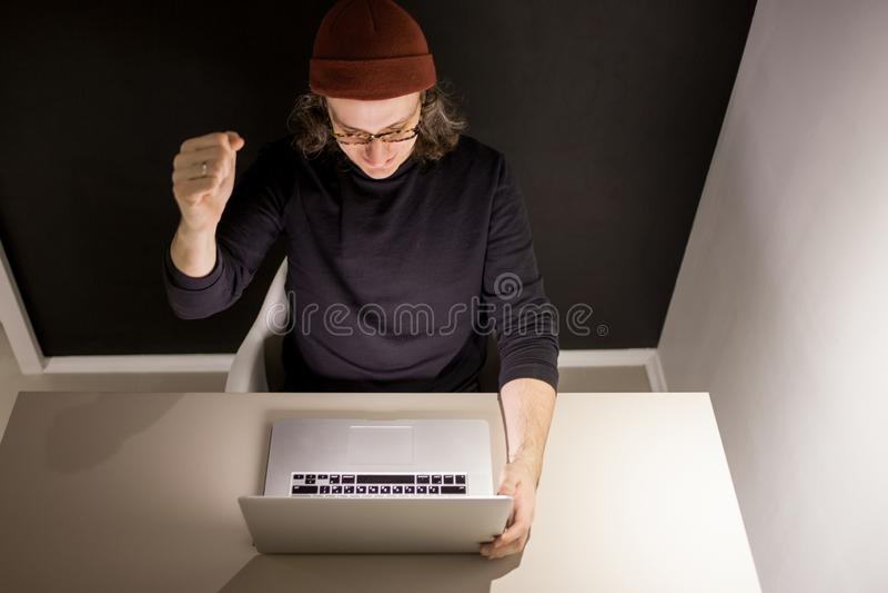 Desenhista ou programador no local de trabalho homem novo em um chap?u e nos vidros que sentam-se em um port?til imagens de stock royalty free