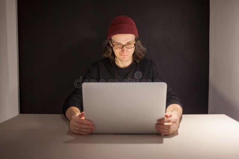 Desenhista ou programador no local de trabalho homem novo em um chap?u e nos vidros que sentam-se em um port?til imagem de stock