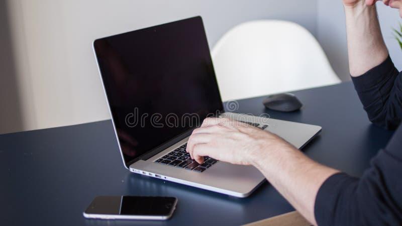 Desenhista para um port?til, um local de trabalho para freelancers Um homem novo que senta-se em uma tabela imagens de stock