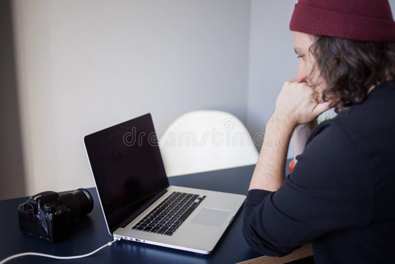 Desenhista para um port?til, um local de trabalho para freelancers Um homem novo que senta-se em uma tabela fotografia de stock