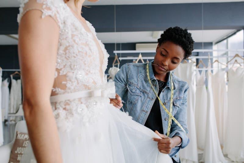 Desenhista profissional do vestido de casamento que cabe o vestido nupcial à mulher foto de stock royalty free