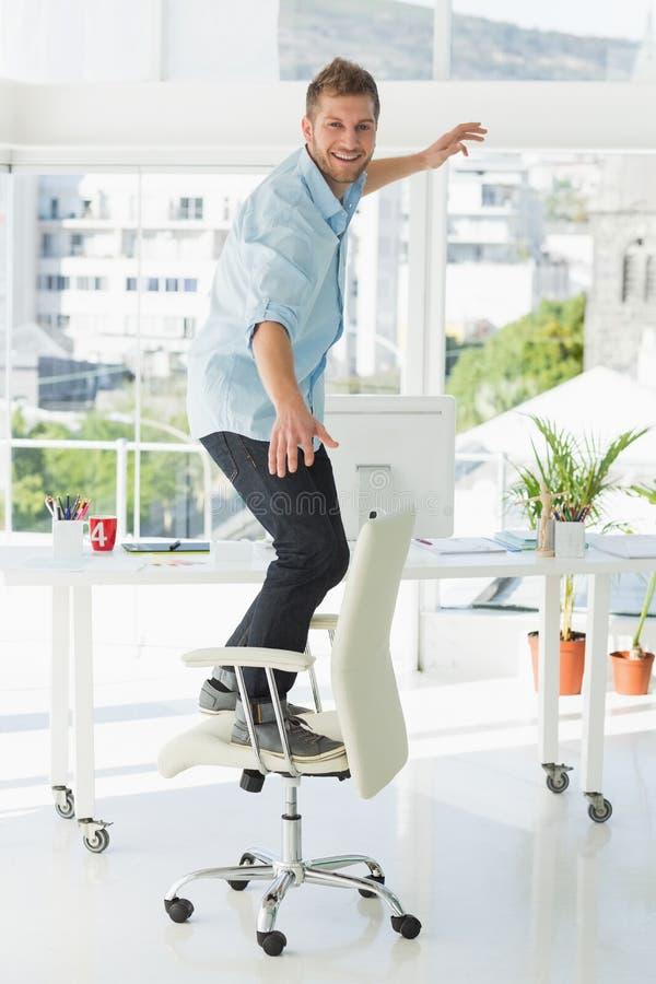 Desenhista que surfa em sua cadeira do escritório fotos de stock royalty free