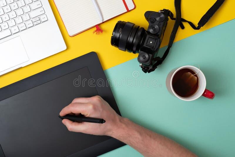 Desenhista que usa a tabuleta gráfica no trabalho e na edição digitais da foto fotografia de stock