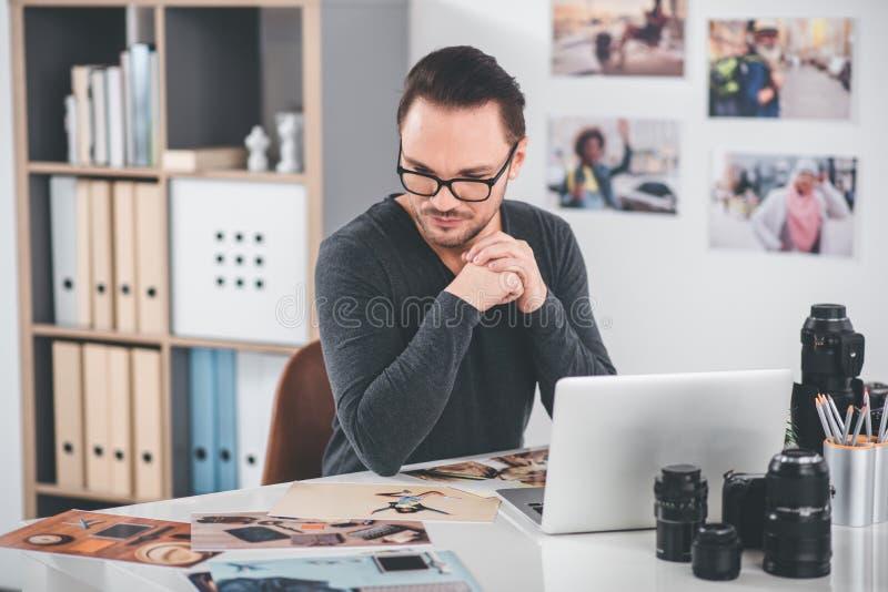 Desenhista sereno que trabalha com imagens na tabela imagens de stock royalty free