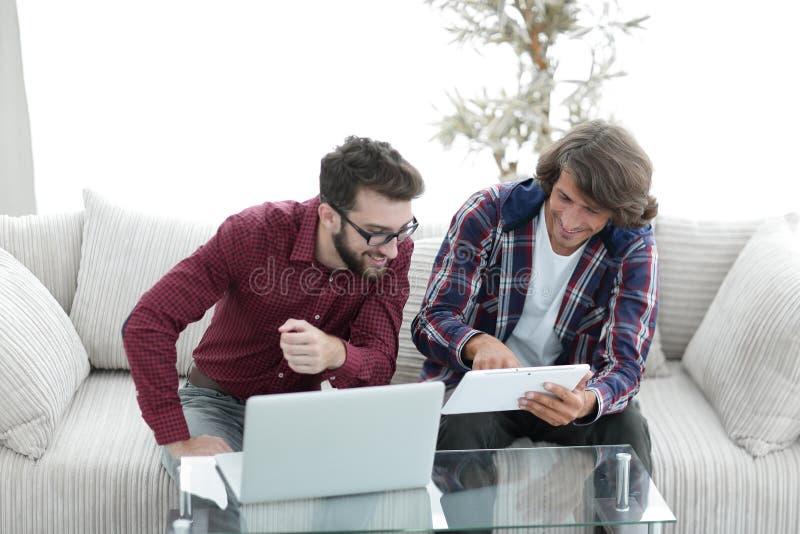 Desenhistas criativos da Web que trabalham com uma tabuleta e um portátil fotografia de stock royalty free
