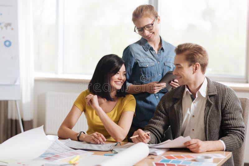 Desenhistas de trabalho duros felizes que falam entre si imagens de stock royalty free