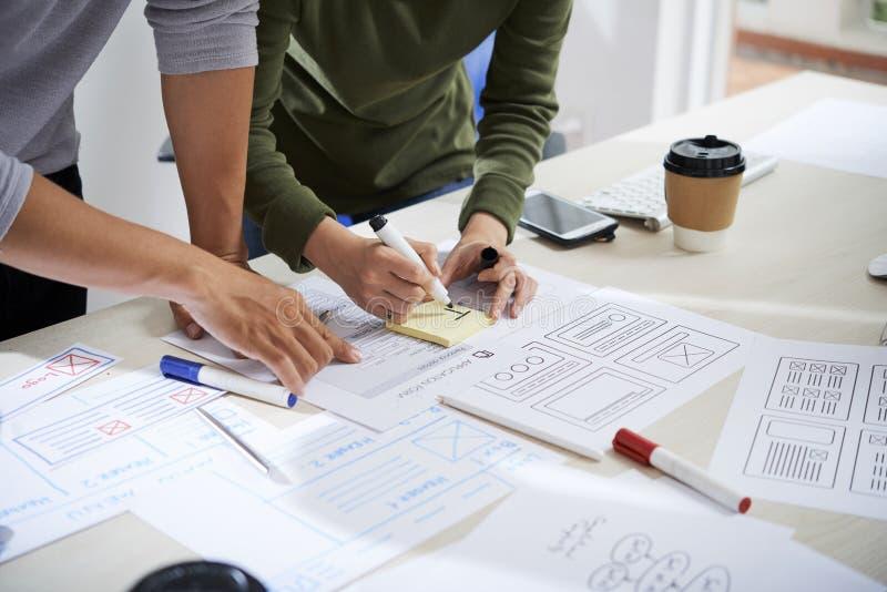Desenhistas de UX que trabalham no projeto do wireframe do Web site foto de stock royalty free