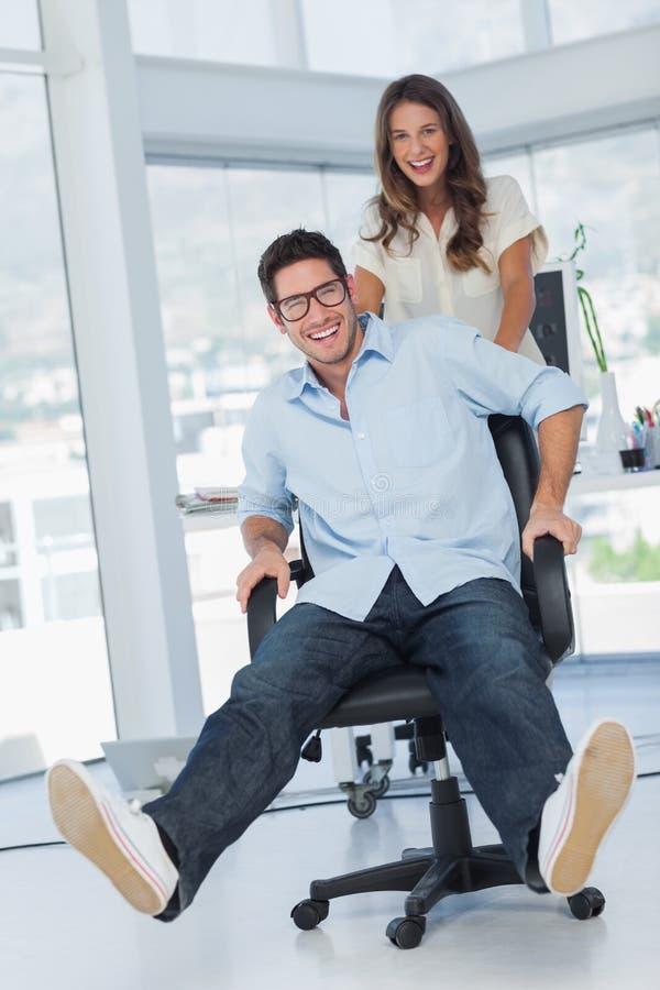 Desenhistas felizes que têm o divertimento com uma cadeira de giro imagem de stock royalty free